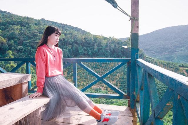 Žena na balkóne s modrým dreveným zábradlím.jpg