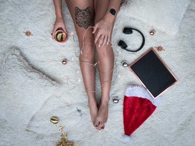 Žena s tetovaním vlka na nohe sedí na posteli s mikulášskou čiapkou.jpg