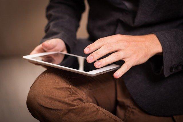 Muž v hnedých nohaviciach a čiernom saku má na kolenách tablet.jpg