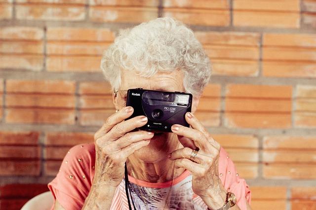 Stará žena fotografuje s malým fotoaparátom.jpg