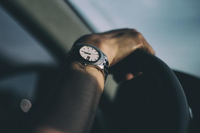Mužská ruka s hodinkami na volante auta.jpg