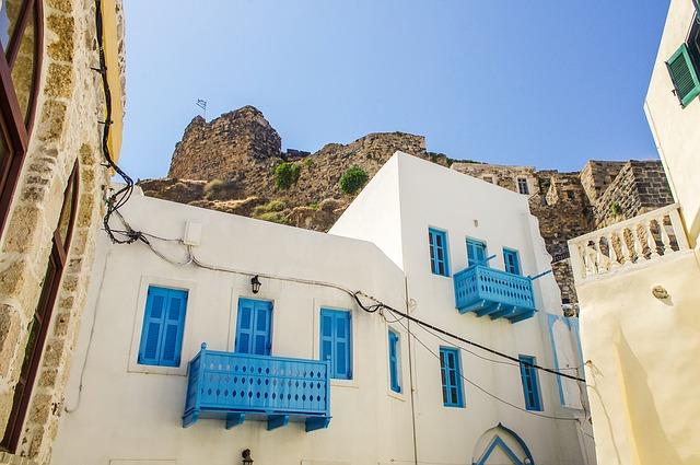 Biela budova s balkónmi s modrým zábradlím.jpg
