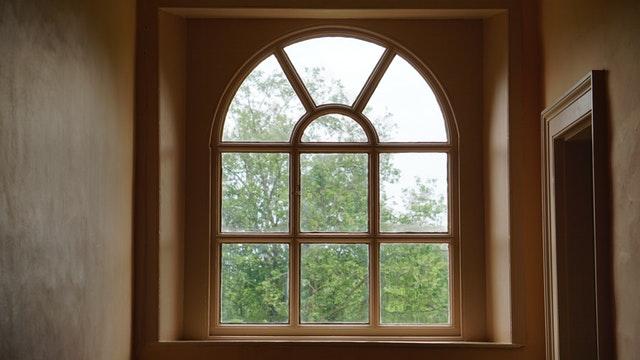 Okno, za ktorým je veľká zelený strom