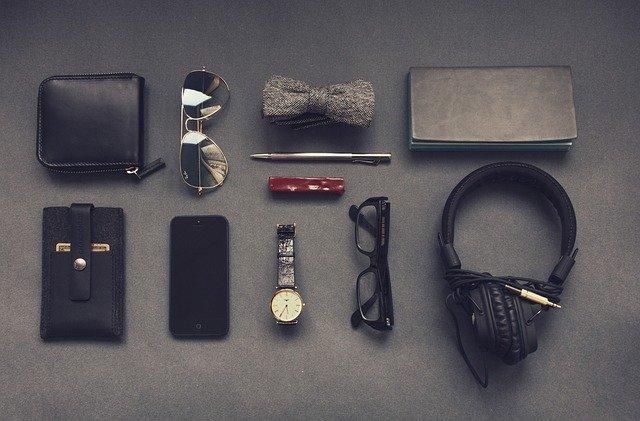 Kožené peňaženky, telefón, motýlik, hodinky a slúchadlá na stole
